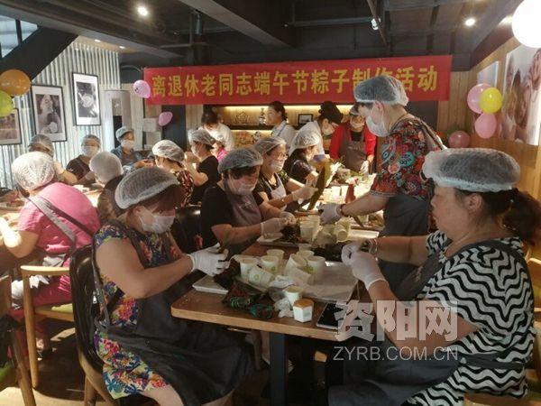 国网资阳市雁江供电公司退休职工在万达广场某蛋糕店学习体验粽子的制作。